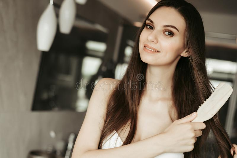 Outgoing woman taking care about hair indoor stock photo
