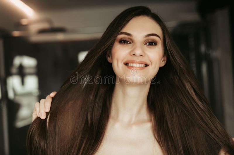 Outgoing female keeping hair in arms indoor royalty free stock image