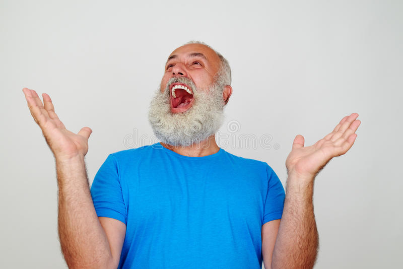 Portrait of bearded aged man who is happy and delighted. By his success stock photo