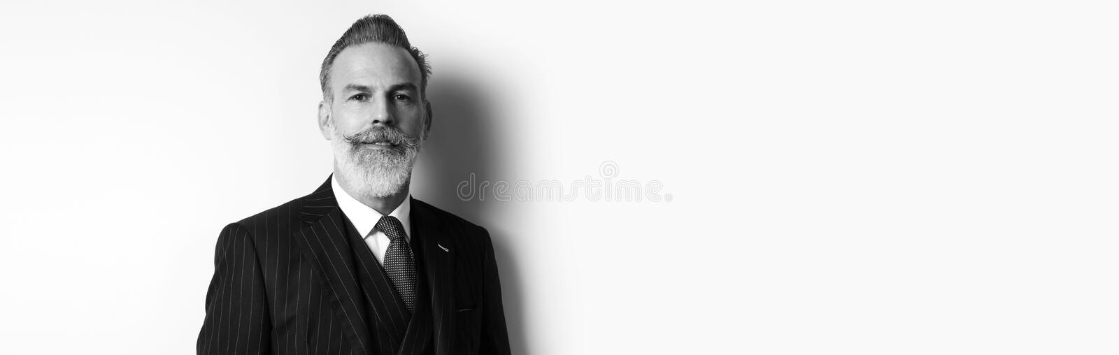 Portrait of bearded attractive businessman wearing trendy suit over empty white background. Copy Paste text space. Wide stock photography