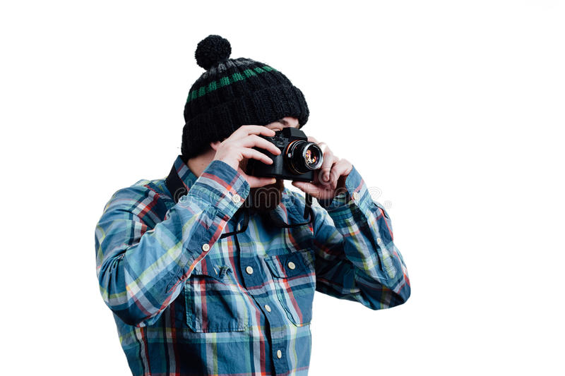 Portrait of a bearded, balding male hipster. White isolated back. Ground. A man in a blue plaid shirt with knitted cap. Holding camera in the hands. Look through royalty free stock photos