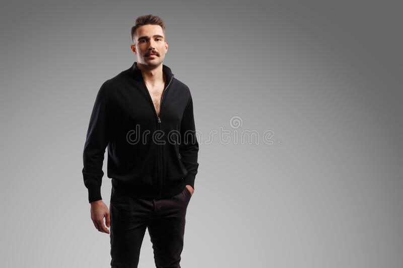 Portrait of a bearded bruntal man in black jacket, with a hand in his pocket, looking at camera over grey background. stock photo