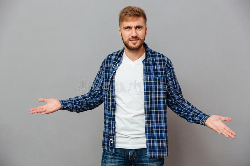Portrait of a bearded casual man shrugging shoulders. Isolated on a gray background royalty free stock image
