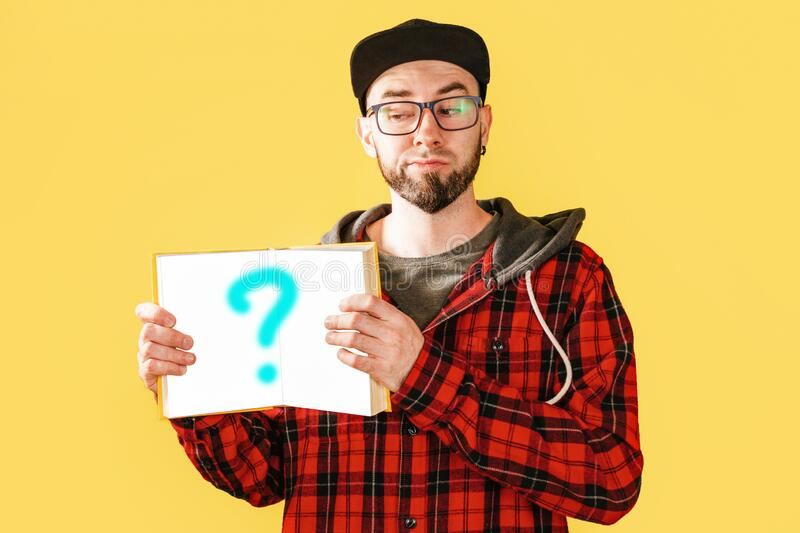 Portrait of a bearded Caucasian man with glasses and a cap holding an open book with sign of question. Yellow background stock photos