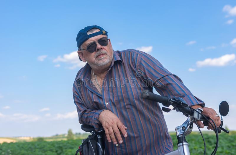 Portrait of a bearded, chubby senior man getting ready to summer ride on a bicycle stock photography
