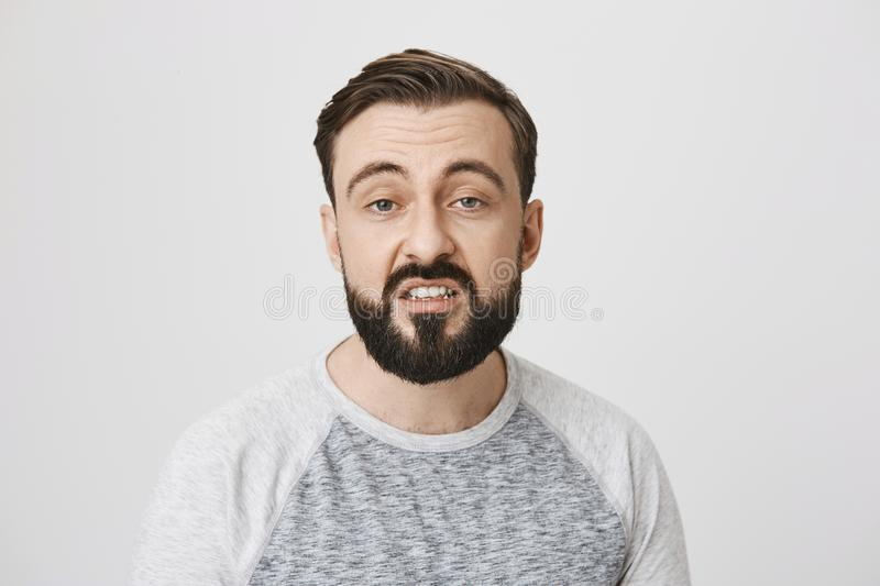 Portrait of bearded european man expressing disgust with opened mouth and fed up expression, standing over gray royalty free stock photography