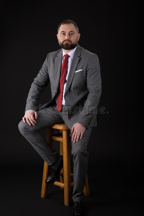 Portrait of a bearded fashion man wearing at suit while seated on a high chair and looking into the camera. on a black background stock images