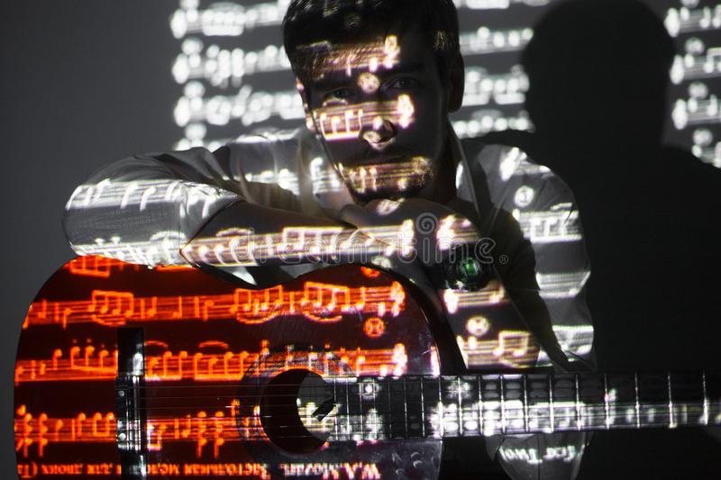 Portrait of the bearded guitar player with projection of the notes. Manis holding his guitar and looking into the camera stock images