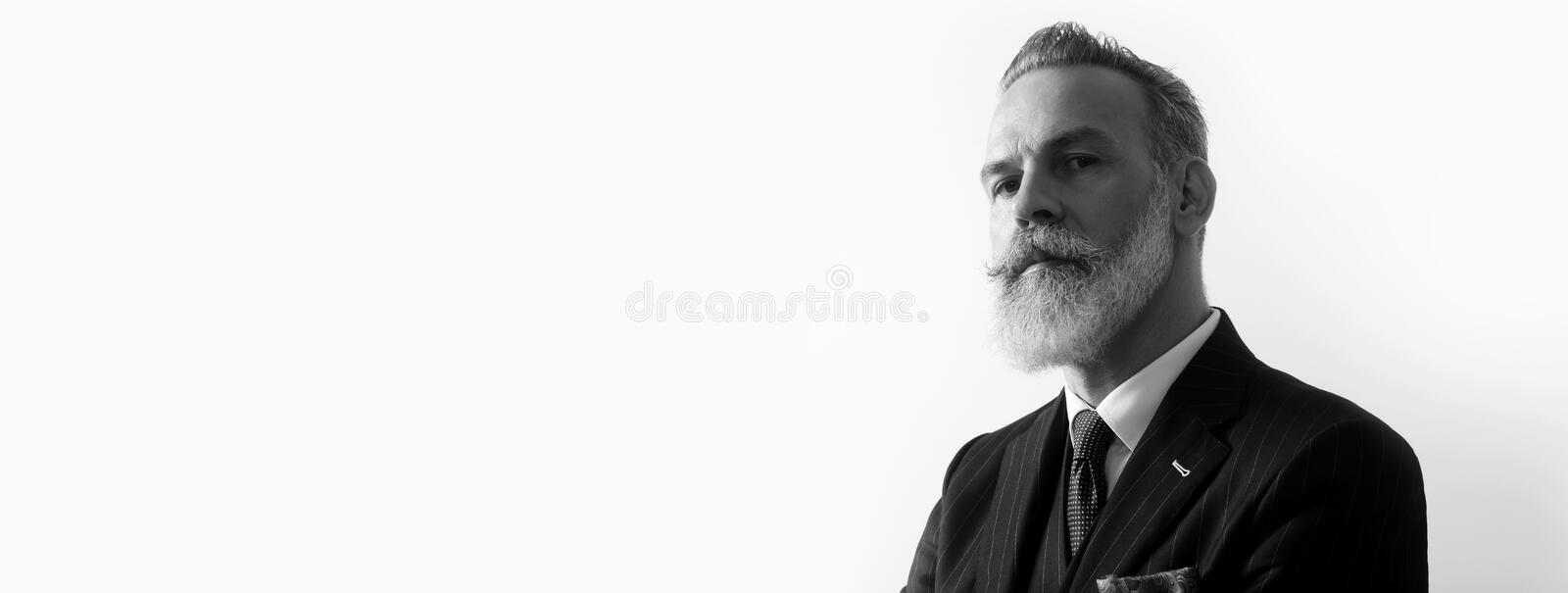 Portrait of bearded handsome gentleman wearing trendy suit over empty white background. Copy Paste text space. Wide. Black and White stock photo