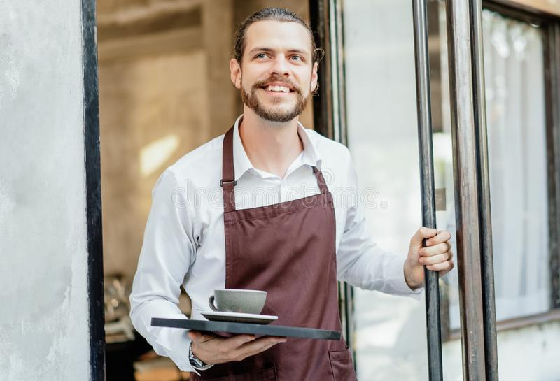Portrait of bearded happy barista man working waitress in cafe open entrance door and serving drinks on a tray in front of the stock photography