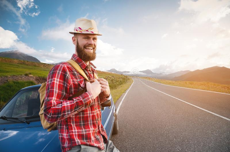 Portrait of a bearded happy smiling traveler hipster with a backpack in a plaid shirt and a hat next to an unknown car royalty free stock photo