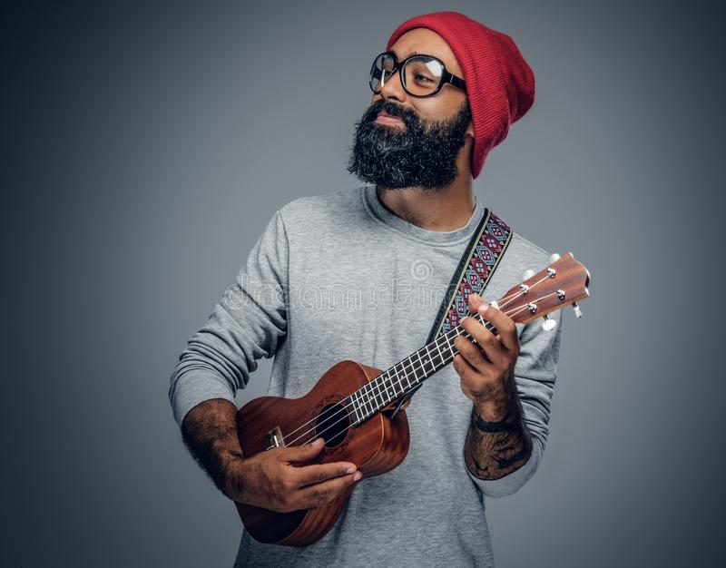 Bearded hipster male in red hat playing on ukulele. Portrait of a bearded hipster male in red hat playing on ukulele. on grey background stock photo