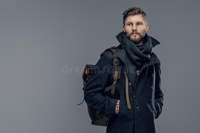 A man dressed in a jacket and scarf. Portrait of bearded male dressed in a warm jacket and a scarf hold a backpack isolated on grey background royalty free stock image