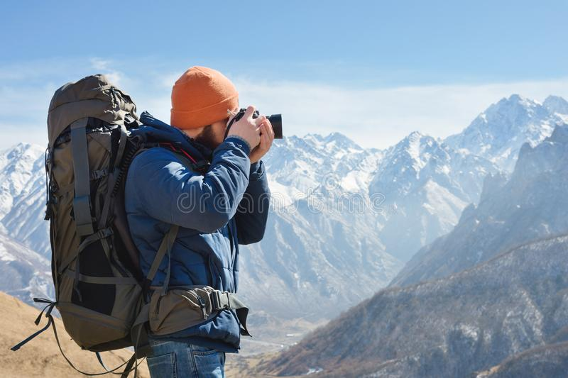 Portrait of a bearded male photographer in sunglasses and a warm jacket with a backpack on his back and a reflex camera royalty free stock images