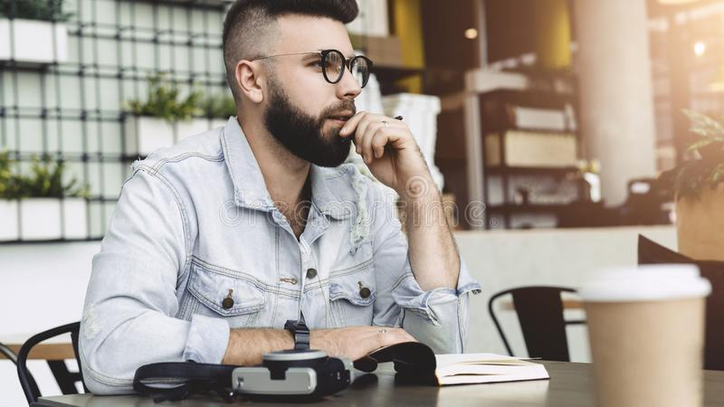 Portrait of bearded male writer. Guy sits with notebook in cafe at table, holds pencil in his hand, looks thoughtfully. stock photos