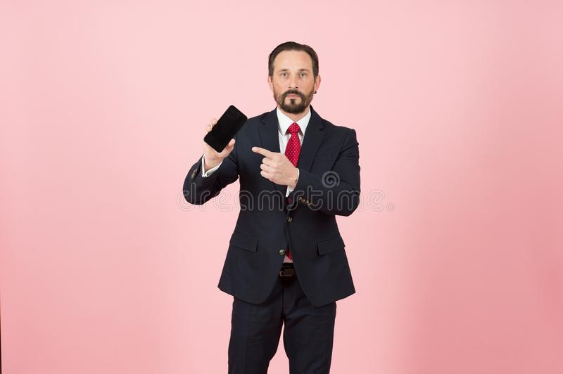 Portrait of seriouse man in black suit pointing finger at blank screen mobile phone isolated over pastel pink background. stock photography