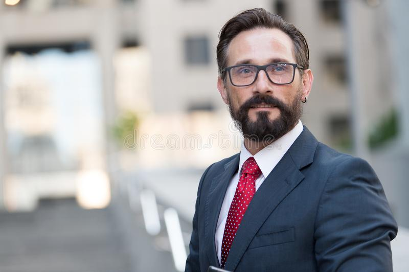 Portrait of bearded man in suit on background of building. Handsome businessman outdoor. Male business person stands on street and royalty free stock photo