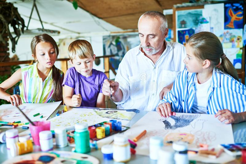 Senior Man Teaching Art Class. Portrait of bearded men teaching group of children painting together at desk in art studio royalty free stock photo