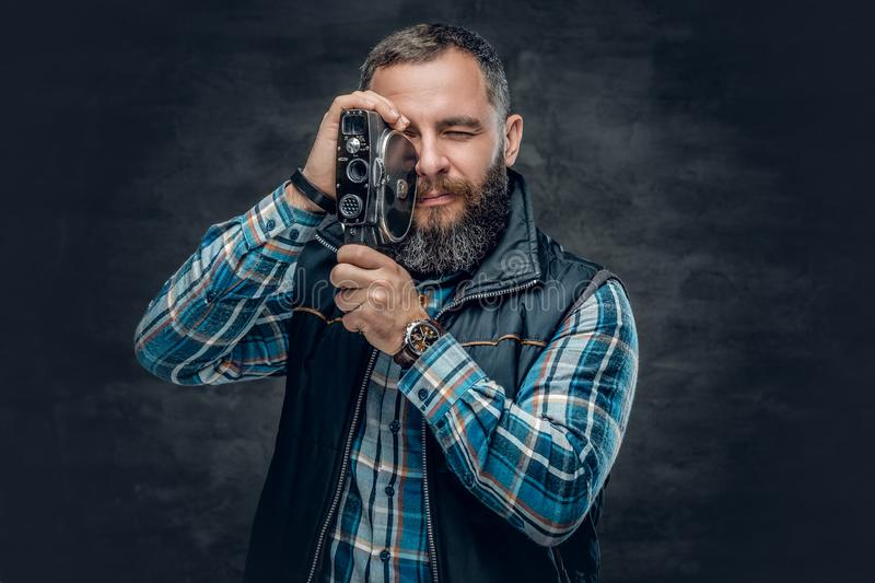 Bearded middle age male holds vintage 8 mm video camera. stock image