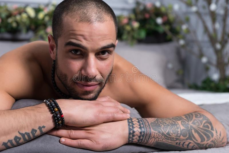 Portrait of bearded muslim man with bare chest and with tattooed stock photography