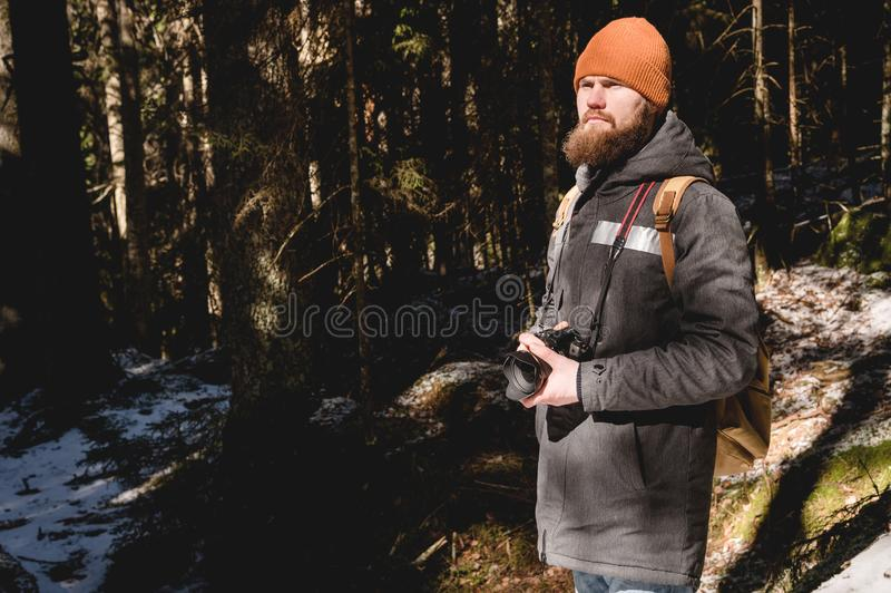 Portrait of a bearded photographer with a reflex camera in his hands in the winter coniferous forest. Photo travel stock photography