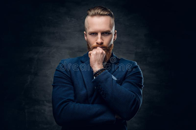 Redhead hipster male dressed in a blue jacket. Portrait of bearded redhead hipster male dressed in a blue jacket over grey background royalty free stock images
