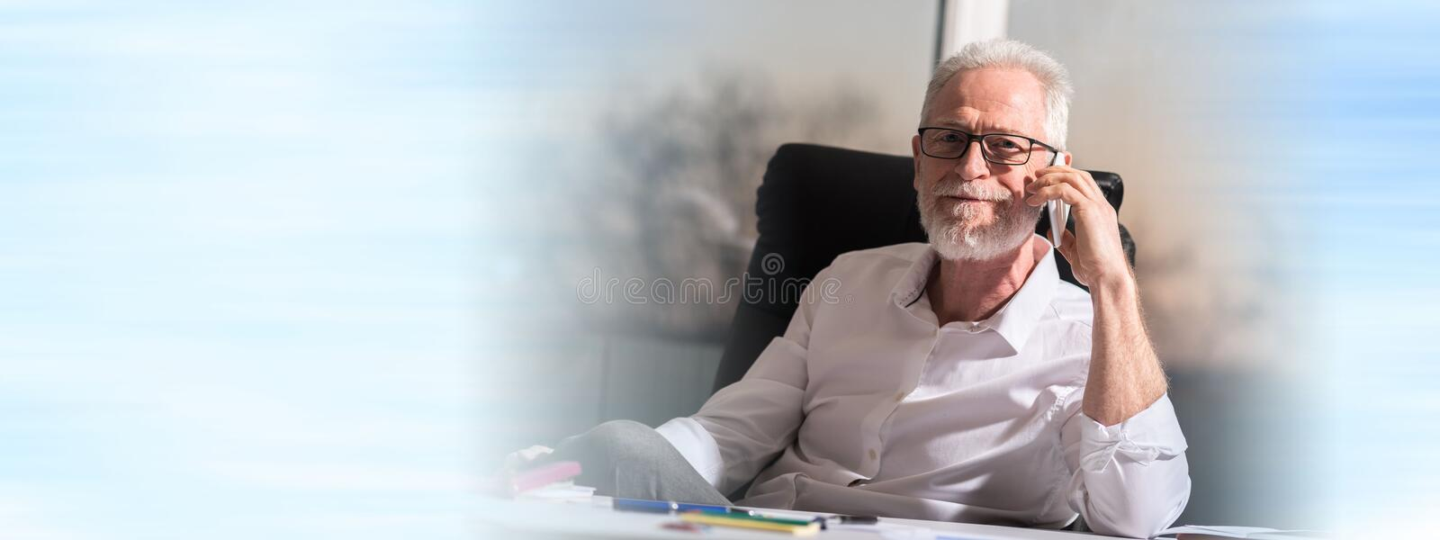 Portrait of bearded senior businessman talking on mobile phone. In office royalty free stock image