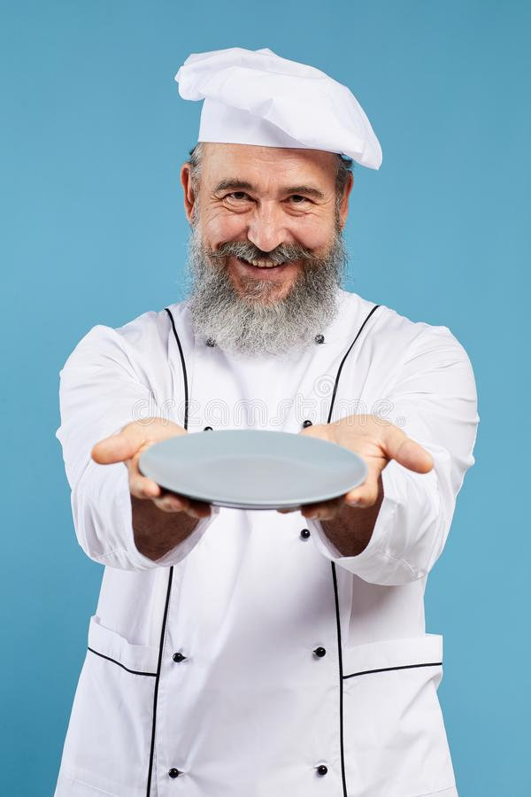 Smiling Senior Chef Holding Empty Plate on Blue stock photos