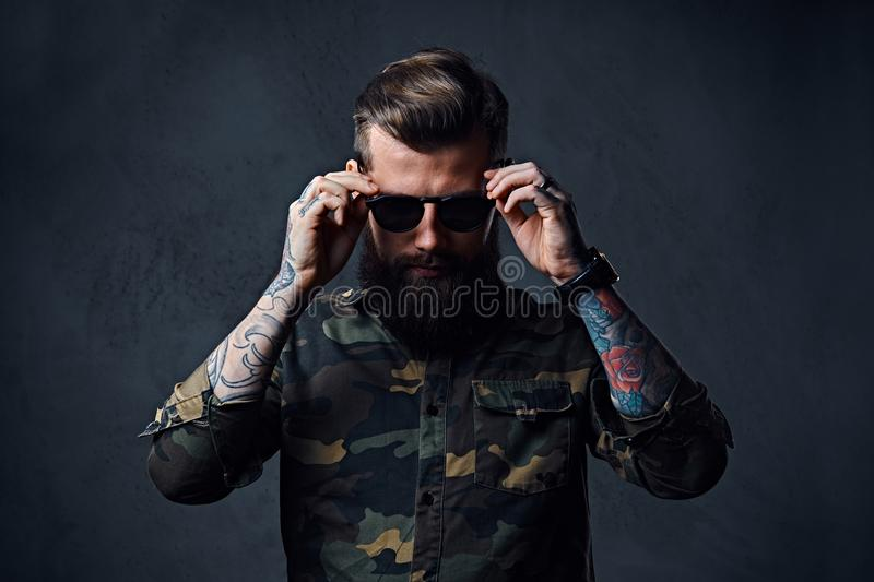 Portrait of bearded tattooed hipster male dressed in a military stock image