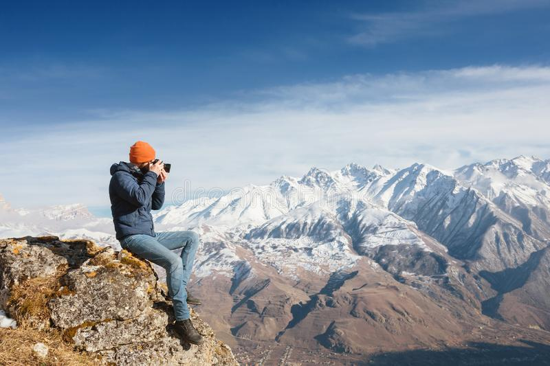 Portrait of a bearded traveler photographer in sunglasses and a cap sits on a rock with mirror camera in his hands royalty free stock photo