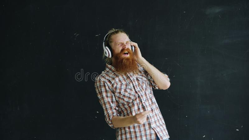 Portrait of bearded young man puts on headphones and dancing while listen to music on black background royalty free stock photos