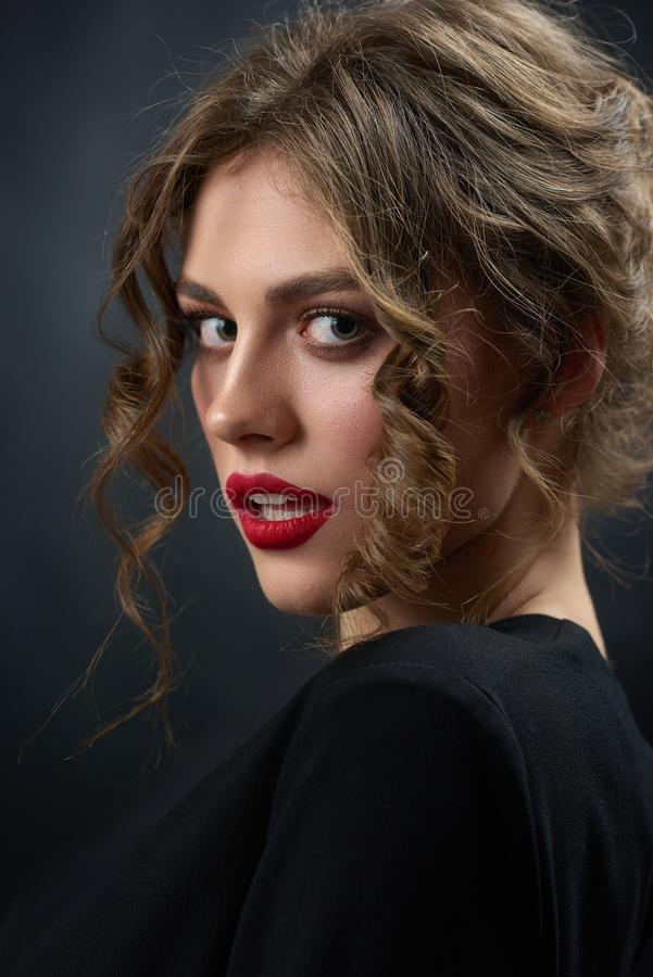 Portrait of passionate woman wearing black shirt and red lipstick. royalty free stock images