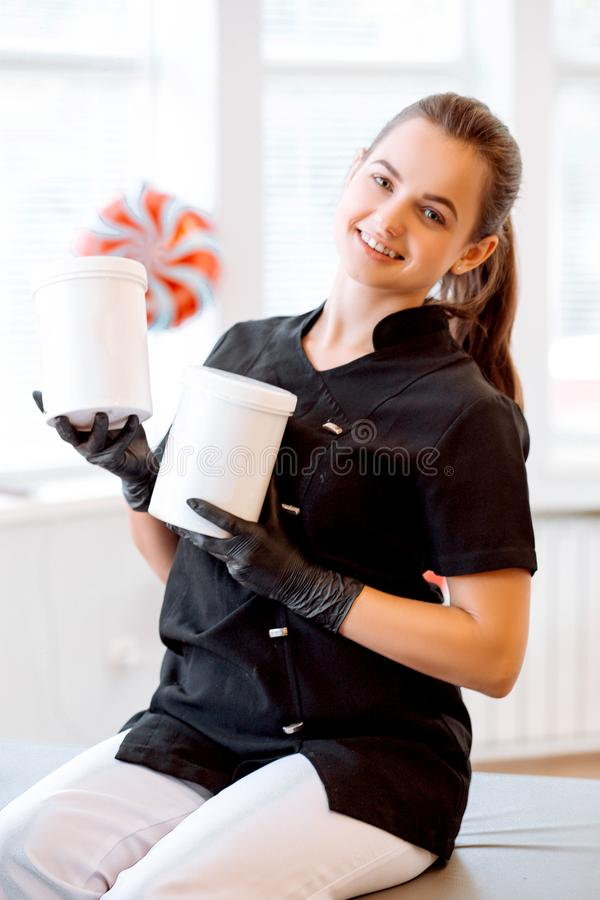 Portrait of a beautician in a black coat, holding a cream jar. She is looking at the camera and smiling royalty free stock image