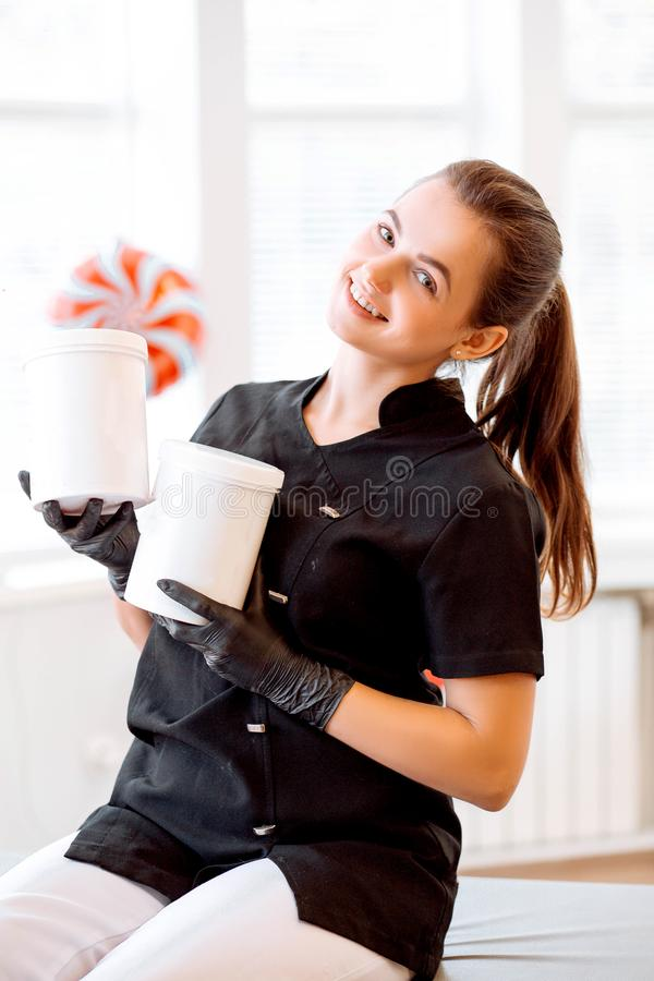 Portrait of a beautician in a black coat, holding a cream jar. She is looking at the camera and smiling stock image