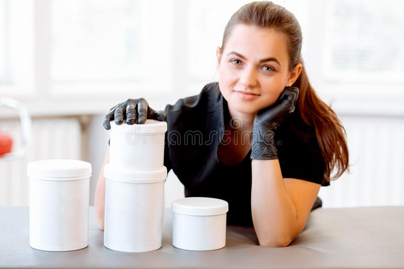 Portrait of a beautician in a black coat, holding a cream jar. She is looking at the camera and smiling stock photo