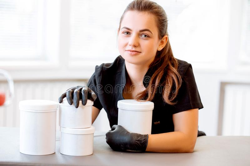 Portrait of a beautician in a black coat, holding a cream jar. She is looking at the camera and smiling royalty free stock images