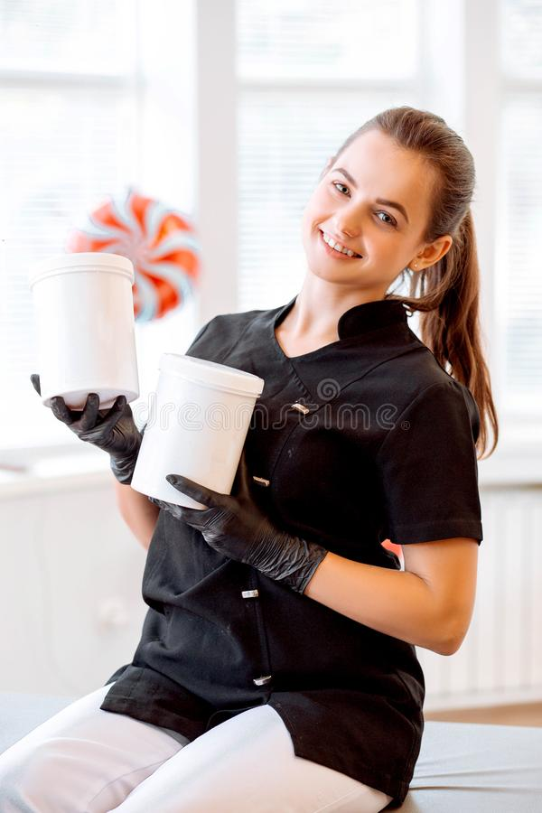 Portrait of a beautician in a black coat, holding a cream jar. She is looking at the camera and smiling royalty free stock photos
