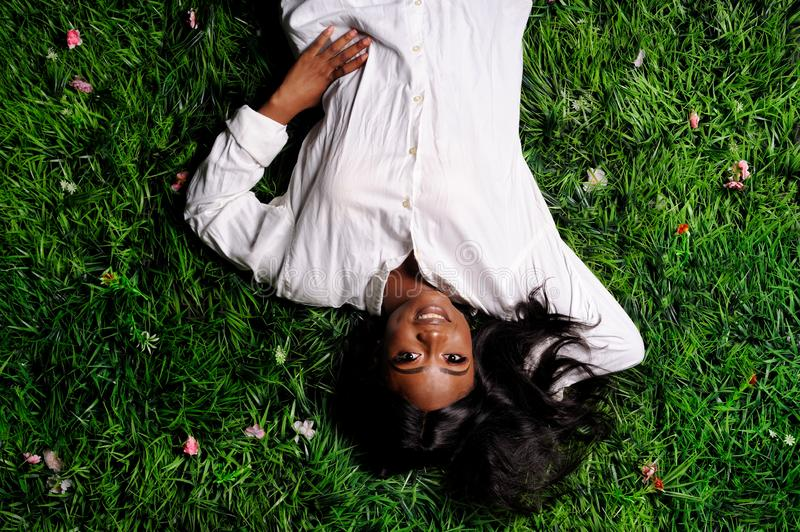 Portrait of beautiful african american woman laying on green grass in park. Female, outdoor, looking, smiling, lifestyle, happy, summer, black, attractive stock photo