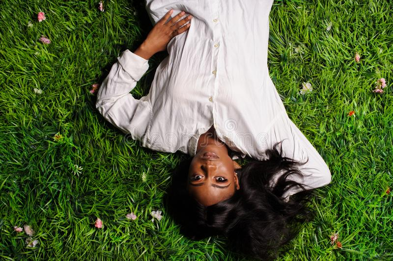 Portrait of beautiful african american woman laying on green grass in park. Adult, afro, attractive, beauty, black, casual, comfortable, cute, enjoyment royalty free stock photos