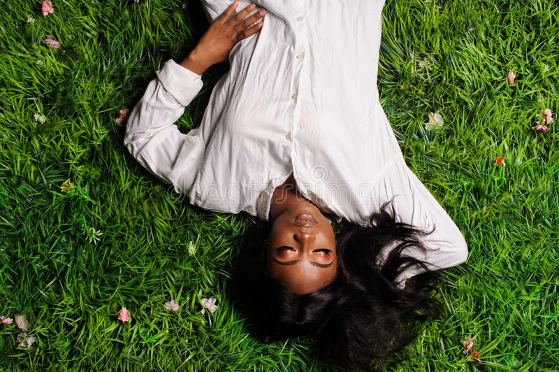 Portrait of beautiful african american woman laying on green grass in park. Adult, afro, attractive, beauty, black, casual, comfortable, cute, enjoyment royalty free stock image