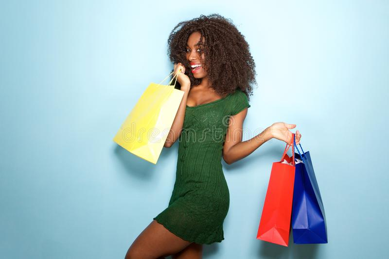Beautiful african girl happy with shopping bags on blue background royalty free stock image