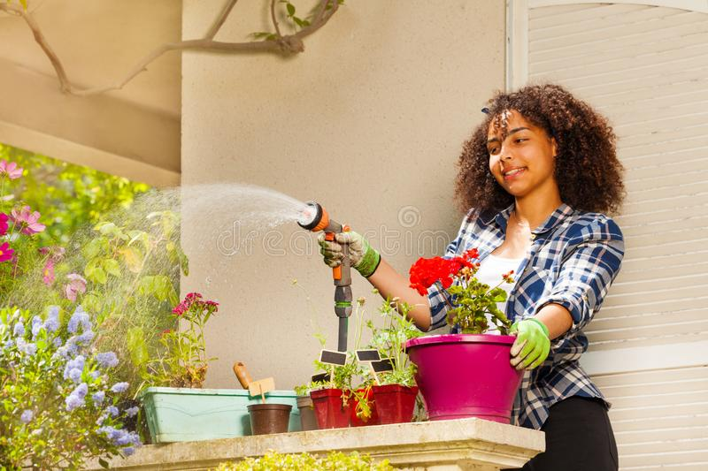 African girl watering flowers standing on terrace royalty free stock images