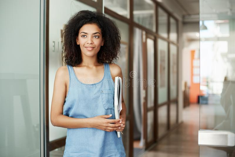 Portrait of beautiful african student girl standing in college corridor smiling holding books looking in side. Education stock photography