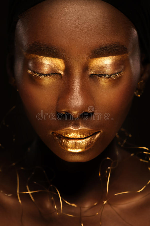 Portrait of beautiful african woman with creative gold make–up and jewelry stock image