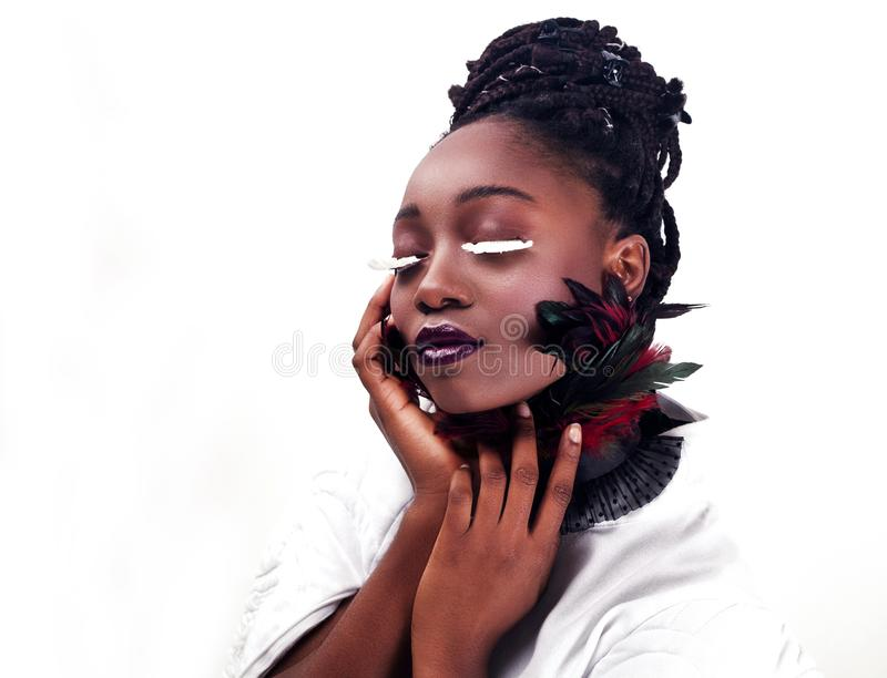 Portrait of a beautiful African woman. Studio with white background. Make up with lashes made of feathers. Fashion style stock image