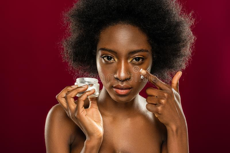 Portrait of a beautiful afro American woman applying cream royalty free stock images