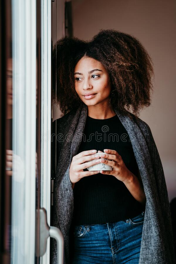 portrait of beautiful afro american young woman by the window holding a cup of coffee. Lifestyle indoors royalty free stock image