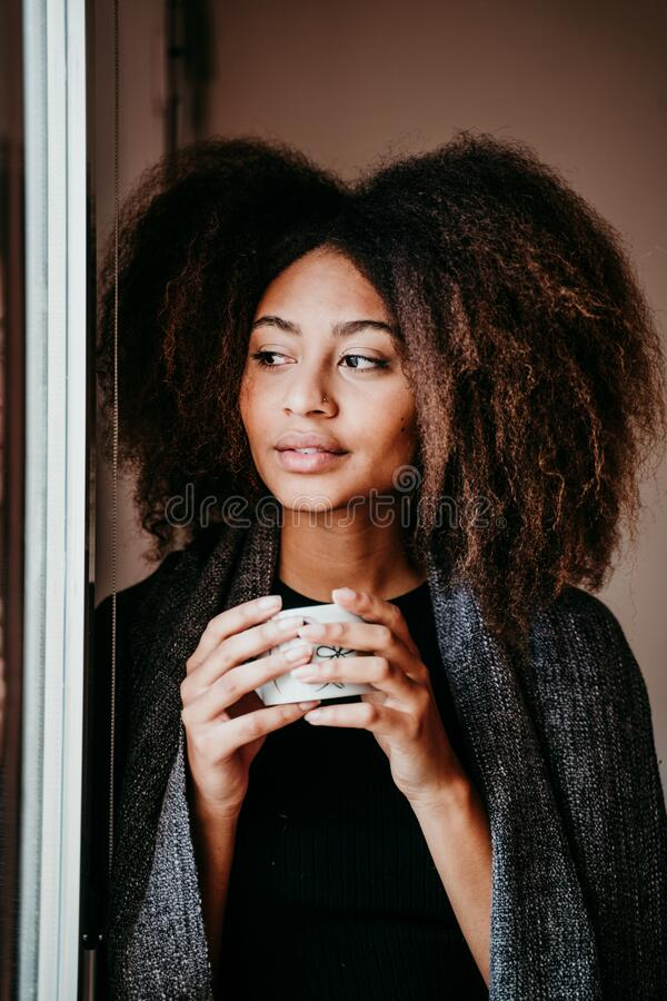 portrait of beautiful afro american young woman by the window holding a cup of coffee. Lifestyle indoors stock photos