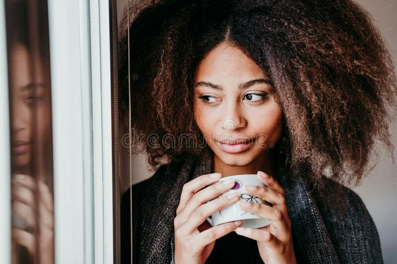 portrait of beautiful afro american young woman by the window holding a cup of coffee. Lifestyle indoors stock photo