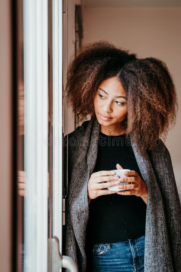 portrait of beautiful afro american young woman by the window holding a cup of coffee. Lifestyle indoors royalty free stock photography